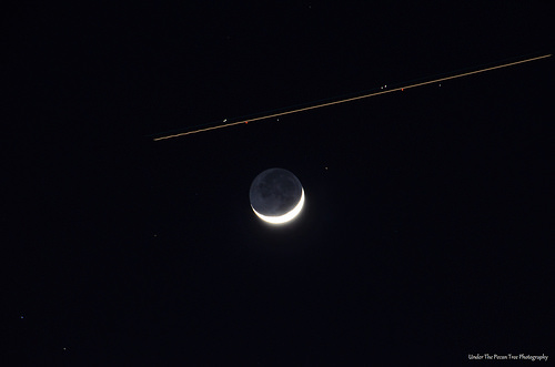The Earth Shine of the Moon with an airplane traveling to DFW Airport
