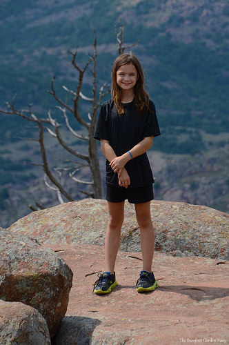 Katelynn is standing on a scenic rock on Mount Scott
