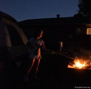 Sara is cooking one of her 'wienie dogs' in the campfire.