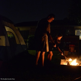 Kevin and Katelynn are tending the campfire.