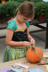Sara decorates her pumpkin with seeds and stickers.