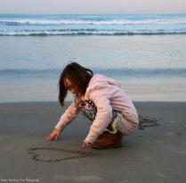 Sara draws hearts and flowers in the beach sand.