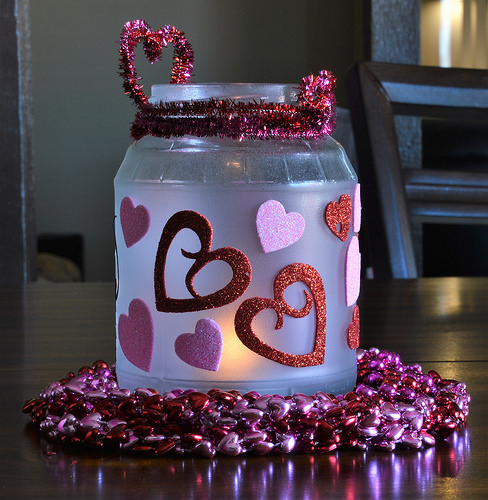 The candle jar is decorated with a lot of heart stickers.