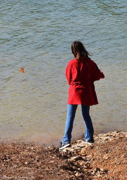Katelynn skips some rocks over the lake surface.