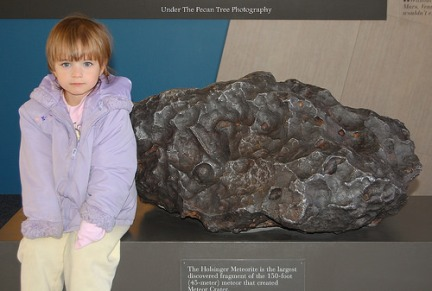 Katelynn sits next to the Holsinger Meteorite, which is the largest fragment discovered from the Meteor impact in Arizona.