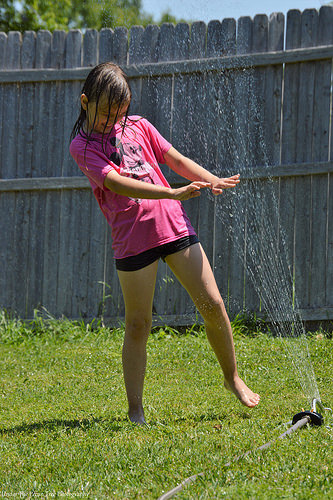 Sara loves playing in the sprinklers.