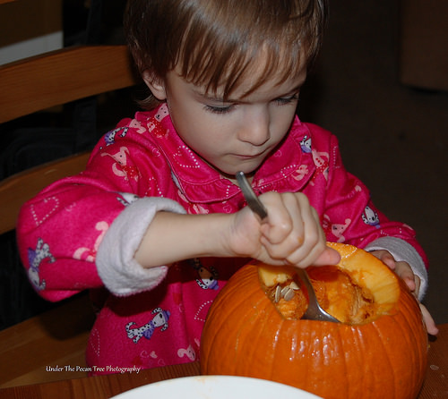 Katelynn helps carving another pumpkin.